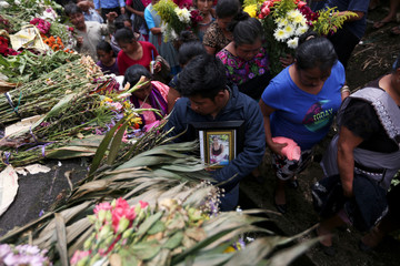 A man holds a picture of Maritza Nij, who died during the eruption of the Fuego volcano, during her funeral in Alotenango