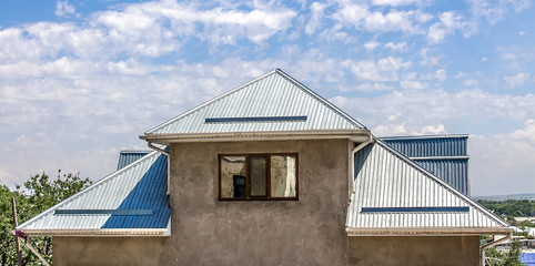 The roof of the house is made of galvanized metal profile against the sky