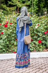 Girl in a Muslim dress in a city park in spring