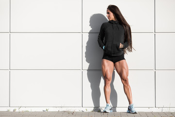Sexy muscular woman with big quads. Athletic girl posing outdoor, muscular legs