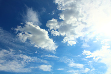A beautiful cloudy sky, cumulus clouds and scorching sun. Background. Landscape.