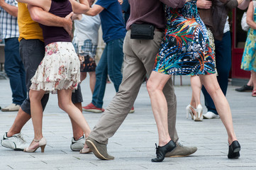 closeup of legs of couple of tango dancers in the street