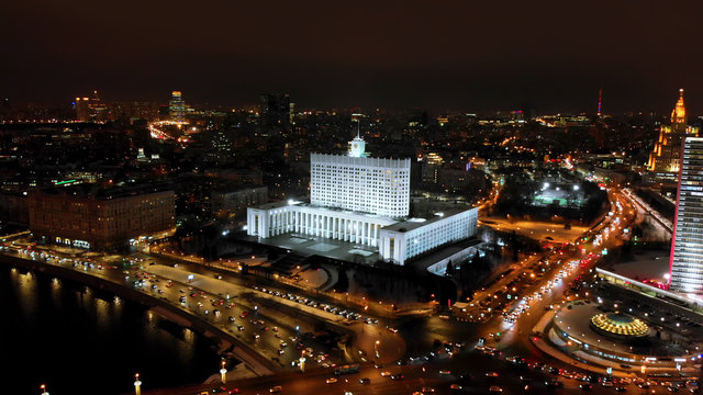 The White House of Russia surrounded by wide streets. Intensive traffic of the city. City panorama with night illumination.