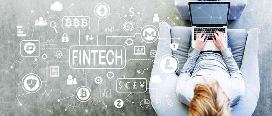 Cryptocurrency Fintech Theme with man using a laptop in a modern gray chair