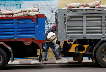 A labourer unloads cement bags from trucks at a construction side in Phnom Penh