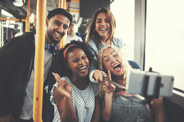 Laughing group of friends taking selfies together on the bus