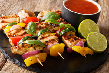 grilled chicken skewers with summer vegetables with sauce, basil and lime closeup. horizontal