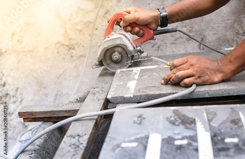 Close up of worker making cut sandstone by electric hand