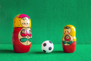 Classic black and white Football soccer ball and three red yellow russian nesting dolls in green background.  Winner, championship, competition concept. Selective focus