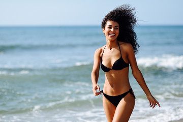 Young arabic woman with beautiful body in swimwear smiling on a tropical beach.