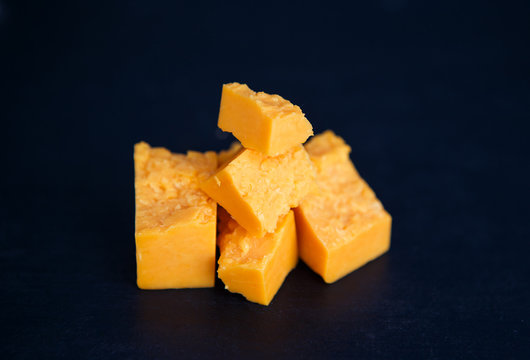 Tasty gouda or parmesan aged cheese in pieces on the black background, horizontal photo. Food and delicatesse concept.