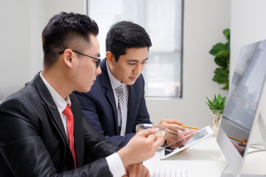 Waist-up portrait of two handsome businessmen in suits sitting at the table with laptop in office interior, talking and looking on each other while discussing a new project