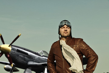 Portrait of a vintage pilot with leather cap, scarf and aviator glasses in front of a historic airplane - Portrait of a man in historical pilot clothing