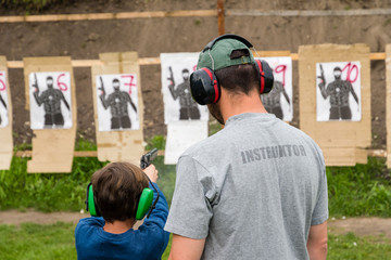 Gun instructor teaching young kid at shooting range