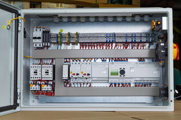 Modern electrical control Cabinet with controller and circuit breakers. Motor protection switches. Contactors with thermal relays. Fuse-operated breakers. Through terminals. Connecting wires.