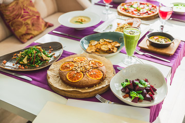 Table in cafe with vegetarian dishes - pizza, salads, pie with citrus and fresh drinks.
