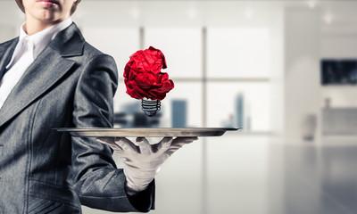 Hand of waiter presenting crampled paper lightbulb