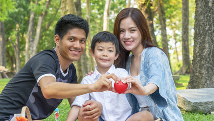 Family Picnic at gaden park Outdoors Togetherness Relaxation Concept with kid hold the red heart symbol.