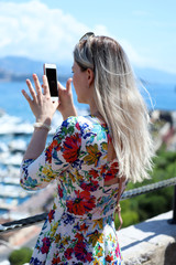 Young Blonde Woman Taking A Picture With Her Smartphone in Monaco