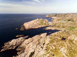 Photo of Lindesnes beacon in summer, South Norway. Aerial shot. Rocky sea coast and blue sky.