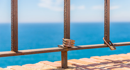 rusty padlock attached to a balustrade by the sea, a traditional way of showing love