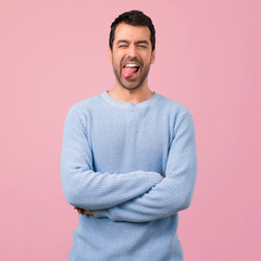Handsome man showing tongue at the camera having funny look on pink background