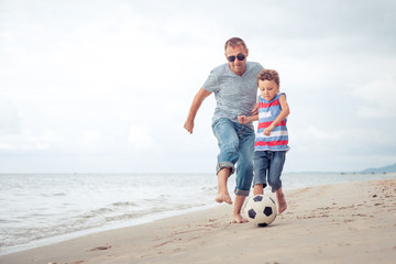 Father and son playing football on the beach at the day time.