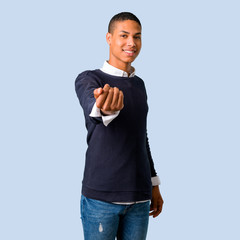 Young african american man presenting and inviting to come on isolated blue background