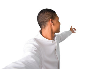 Young african american man  taking a selfie with the mobile presenting and inviting to come with hand on isolated white background