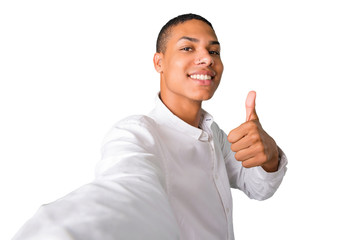 Young african american man  taking a selfie with the mobile and giving a thumbs up gesture while and smiling. Cheerful expression on isolated white background