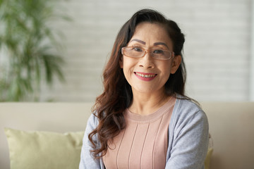 Portrait of Asian smiling mature woman sitting at home