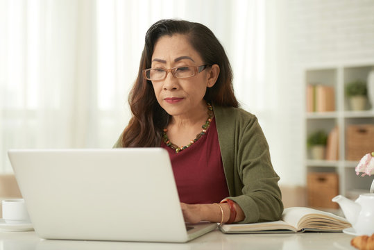 Mature woman in eyeglasses using laptop at the table at home