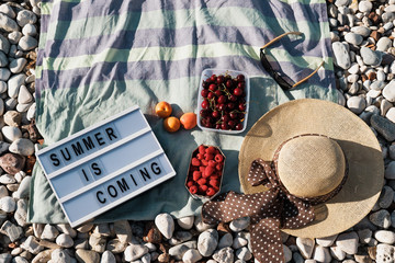 Summer composition with hat, berries anSummer composition with Letter Board Quote, hat, berries and sunglasses on a pebbles beach near sead sunglasses on a pebbles beach near sea