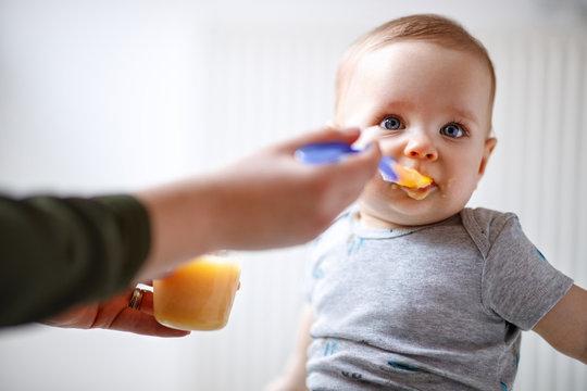 Mother feeds baby with fruit porridge