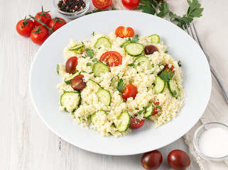 fresh diet vegetable salad with couscous, tomatoes, cucumbers, parsley, white wooden table, side view