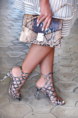 Elegant modern fashion women's accessory. Caucasian lady wearing high heel black- snake skin strappy sandals and white dress holding snake skin leather purse. Fashion concept, catwalk