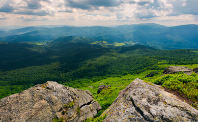 rocks on the edge of a  mountain. location Pikui mountain. Runa mountain in the far distance. Beautiful summer landscape of Carpathian mountains on a cloudy day