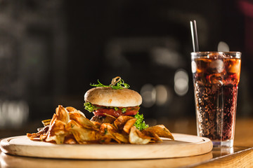 A delicious fresh hamburger with Coca Cola on a bar counter