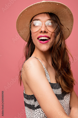 621b148e7d3e Inspired european female model looking aside with happy smile and true  emotions in studio and laughing. Winsome brunette girl in cute dress posing on  pink ...
