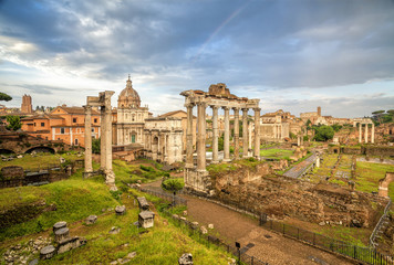 View of the temple of Saturn in Roman forum, Italy. Ruins of Septimius Severus Arch and Saturn Temple. Rome architecture and landmark.