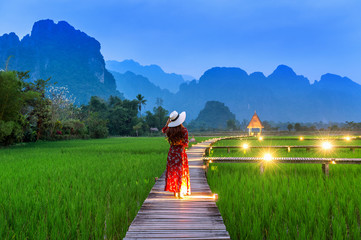 Wall Mural - Young woman walking on wooden path with green rice field in Vang Vieng, Laos.