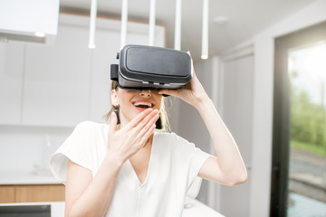 Young excited woman using VR glasses at home