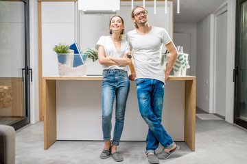 Young and happy couple enjoying their new modern apartment standing at the kitchen with different home stuff on the background