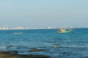 Boat is fishing in front of blur city background