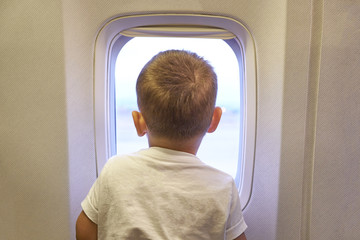 Cute little Asian toddler baby boy child during flight on airplane. Flying with children, Happy air travel with kids & little traveler concept