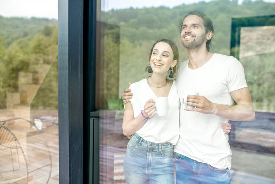 Young and lovely couple standing together looking outside the window at home, view through the window vith reflection