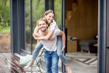 Happy lovely couple having fun playing together on the terrace outdoors of the modern house