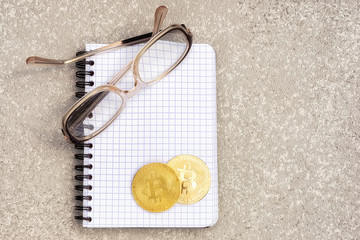 bitcoins on a little notebook with glasses, on a table, top view with copy space