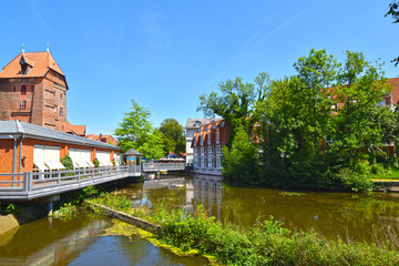 """View on the river Ilmenau in the German medieval town of Lueneburg. The tower of the """"Abtsmill"""" on the left."""