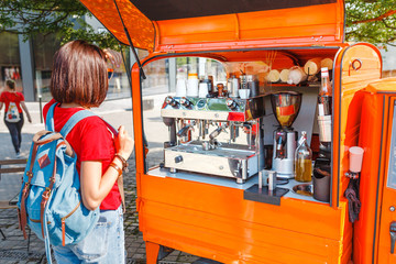 Woman tourist selects coffee in a mobile cafe on wheels, fastfood startup concept
